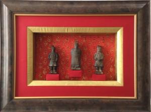Encadrement de trois statuettes de guerriers chinois. Utilisation de différents papiers rouge, doré et à motif doré.